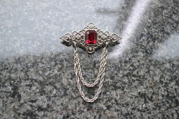 Broche m. rød sten og kæder
